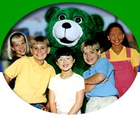 Elementary age children pose with character education-teaching green bear - Kelly Bear